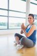 Smiling woman sitting in yoga pose