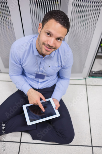 Smiling man using tablet pc beside servers