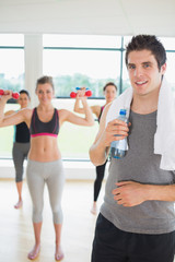 Man standing at the gym holding a bottle of water