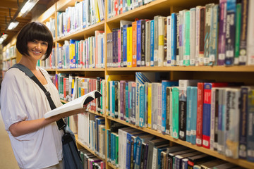 Woman holding a book next to a shelf