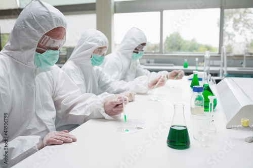 Three chemists working in protective suits