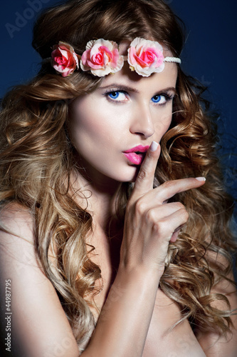 Beautiful woman with long , shiny hair and flowers on nead.