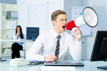 unzufriedender geschäftsmann schreit ins megafon