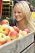 Junge Frau kauft Äpfel