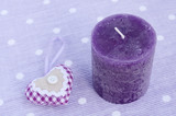 Purple candle and decorative aroma heart on lavender background