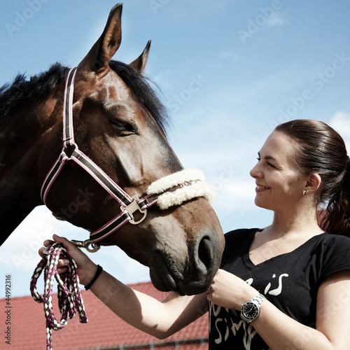 Pretty woman proudly presents her horse outdoors