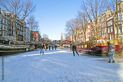 Foto op Aluminium Amsterdam Ice skating on the canals in Amsterdam the Netherlands in winter