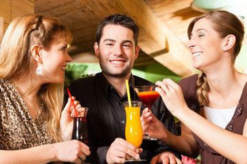 Young people drinking cocktails in bar or restaurant