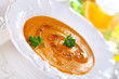 Pumpkin soup with orange juice in white plate, soft focus.