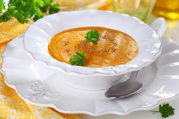 Pumpkin soup in white bowl, soft focus.