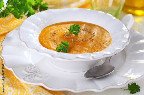 Pumpkin soup in white bowl, soft focus.