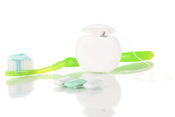 Toothbrush, chewing gum and dental floss isolated on white