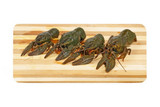 Four uncooked crawfishes on a wooden board.