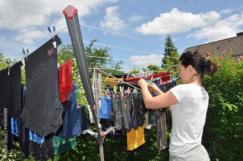 Frau beim Wäsche aufhängen im Garten
