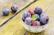Plums on shabby wooden table