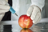Red apple in genetic engineering laboratory, gmo food concept poster