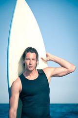Attractive young surfer portrait at the beach with a surfboard.