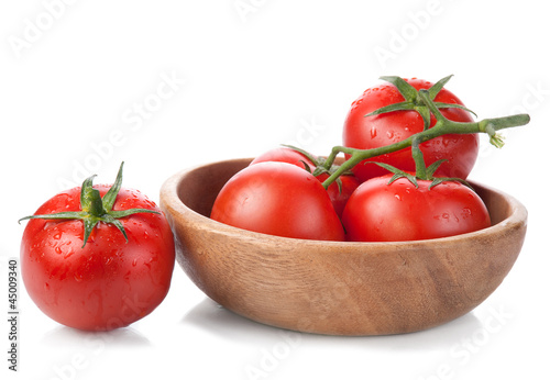 brush tomatoes in a wooden bowl isolated on white background