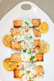 Cooked salmon fillets with spinach sauce on white plate