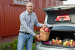 Guy puts apples in the trunk of car