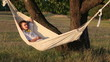 Young man swinging on hammock at sunset