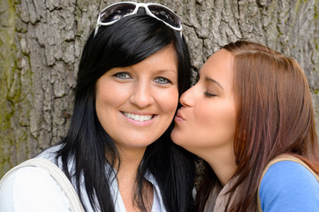 Daughter giving her mother a kiss outdoors