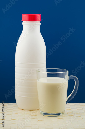 a bottle of milk with a cup on a blue background and a wicker ta