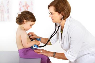 Eine Ärztin hört ein Kind mit dem Stethoskop ab