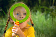 Девочка смотрит удивленно через лупу