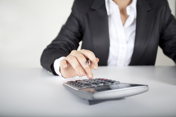 Woman's fingers are on the calculator keys-Horizontal