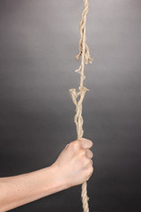 Breaking rope and hand on grey background