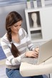 Pretty woman typing on laptop at home