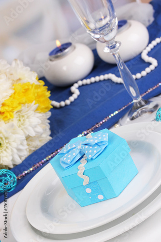 Blue gift for guests on wedding table close-up