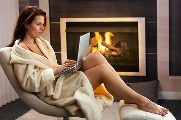 Hot woman with laptop in front of fireplace