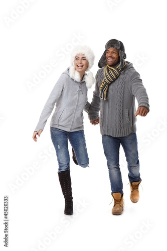 Happy couple running at wintertime