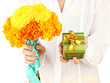 woman holds a box with a gift and flowers