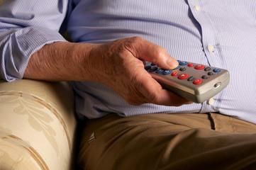 Senior beim fernsehen mit Fernbedienung