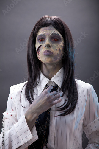 Business woman zombie fastening tie