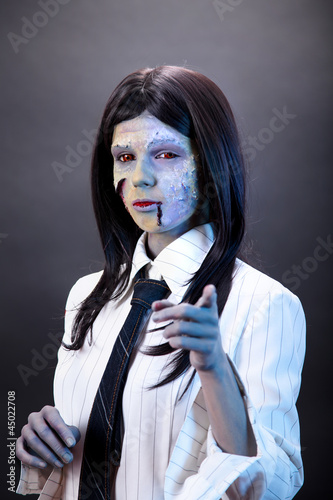 Funny zombie business woman pointing in camera