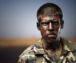 young soldier with camouflage paint looking very serious against