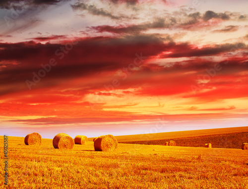 red sky over hay bales
