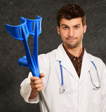 Portrait Of A Young Doctor Holding Crouches