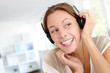 Cheerful young woman listening to music with headphones