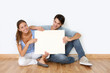Couple sitting on the floor with message board