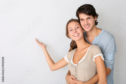 Young couple on white background designating message