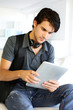 Handsome guy listening to music on internet with tablet