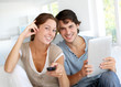 Cheerful couple choosing tv program on digital tablet