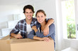 Smiling couple leaning on boxes in new home