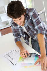 Cheerful young man looking at colours sample for new home