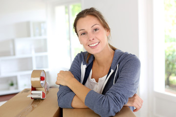 Smiling young woman packing boxes to move out